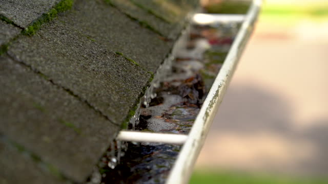 clogged roof gutter and drain pipe with leaves and water - pioggia torrenziale video stock e b–roll