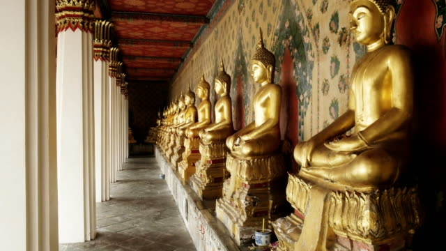 cloister containing many buddha statues at wat arun temple in bangkok - юго восток стоковые видео и кадры b-roll