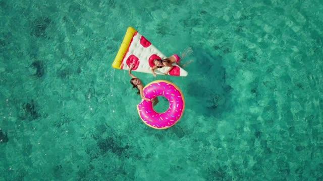 vídeos de stock, filmes e b-roll de feche a vista aérea de duas meninas, nadar e brincar no mar com insufláveis. - inflável