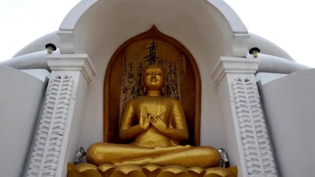 close approach to buddhist stupa with golden buddha statue - buddha video stock e b–roll