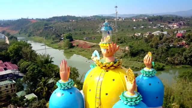 close circling pagoda domes with hands sculptures NHA TRANG/VIETNAM - MARCH 15 2018: close circling inspiring modern pagoda yellow and blue domes with hands in praying positions on top on March 15 in Nha Trang sri lankan culture stock videos & royalty-free footage