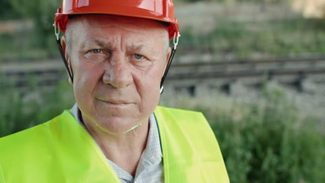 Close confident look into camera of senior railroader in uniform at railway video
