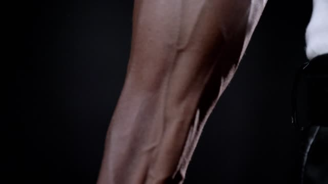 Close footage of african man's vascular strong hand, beautiful muscular body, isolated on black background