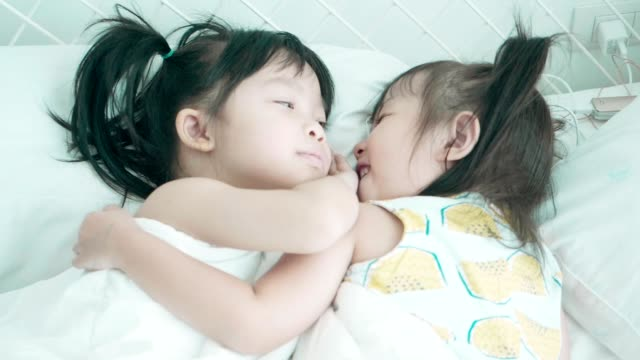 Close friend: Two cute Thai baby girl embracing with love at the bedroom video