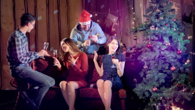 Close friends celebrate Christmas near a fir tree. video