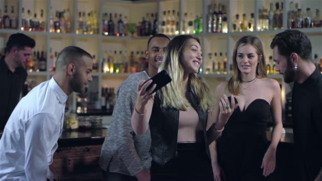 vídeos de stock, filmes e b-roll de amigos próximos amontoam para tomar uma selfie num bar. linda mulher asiática, olhando a foto do seu celular - costumer