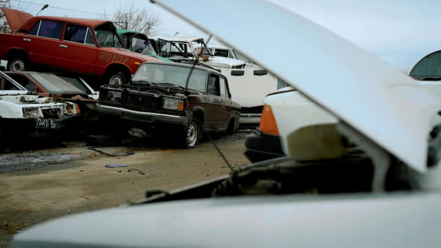 Close look at the wrecked cars on scrapyard under the sky video