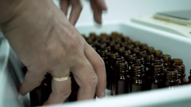 컨테이너에 작은 병을 준비하고 채워질 준비를하는 의료 종사자의 면밀한 모습 - 칸나비디올 스톡 비디오 및 b-롤 화면