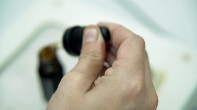 제약 cbd 오일로 dropper 및 충전 병을 사용하여 과학자 손의 가까운 모습 - 칸나비디올 스톡 비디오 및 b-롤 화면