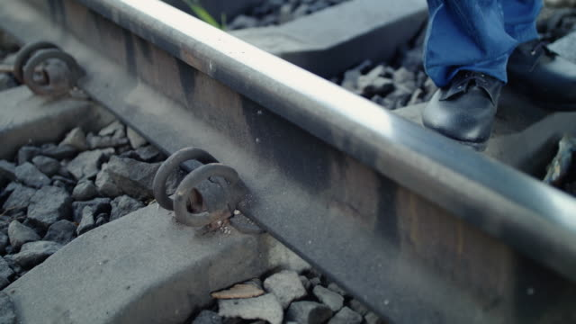 Close low view of railroader checks the rails serviceability with hammer video