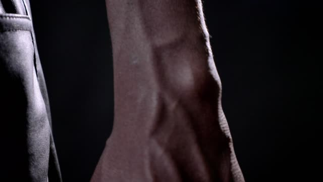 close moving footage of black man's vascular and strong hand, beautiful muscular body, black studio background - naczynie krwionośne filmów i materiałów b-roll