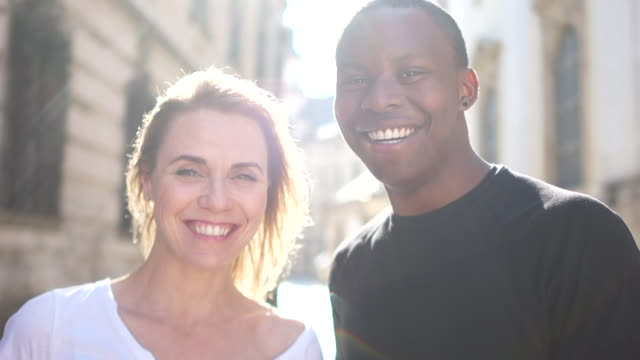 Close outdoor portrait of a happy man and woman. A black guy and a white girl are smiling. Black and white couple in love, sun rays