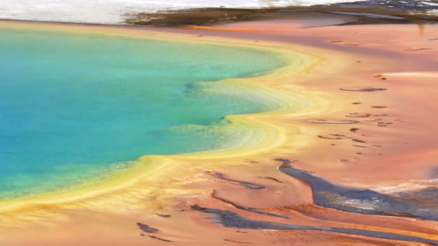 close pan of the east side of grand prismatic pool - источник стоковые видео и кадры b-roll