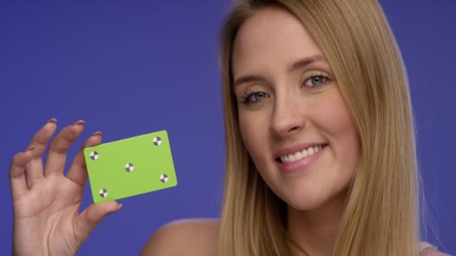 Close Portrait of a beautiful Woman looking at blank credit card which she is holding with one hand Close Portrait of a beautiful Woman looking at blank credit card which she is holding with one hand business card stock videos & royalty-free footage