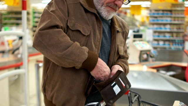 close portrait of an elderly man with a purse in his hands in the supermarket. pensioner smiles - unemployment stock videos & royalty-free footage