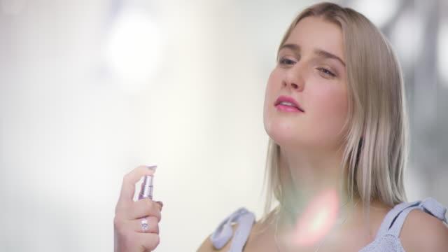 vídeos de stock e filmes b-roll de close portrait of beautiful young woman spraying on perfume on neck - perfume