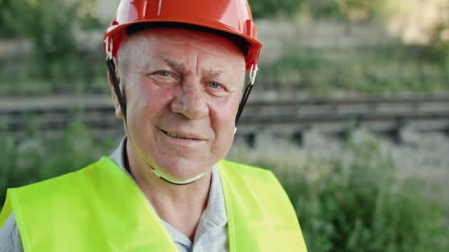 Close portrait of senior railroader in uniform turns at camera and smiles video