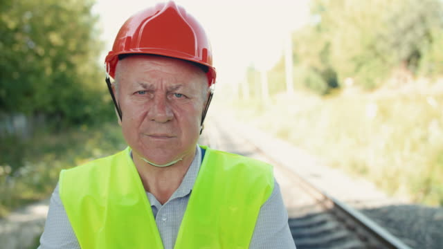 Close portrait of thoughtful senior railroader in uniform looking at camera video