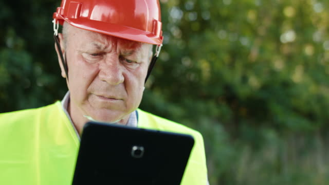 Close portrait of thoughtful senior railroader in uniform types on the tablet video