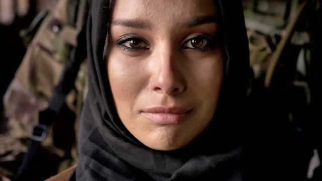 close portrait of young muslim woman in hijab crying and looking at camera, armed soldier with weapon standing behind woman, war - fuggitivo video stock e b–roll