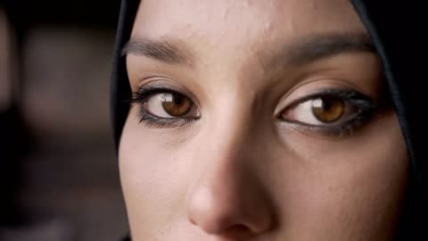 Close portrait of young muslim woman's eyes looking at camera in hijab, sad and depressed expression Close portrait of young muslim woman's eyes looking at camera in hijab, sad and depressed expression. middle east stock videos & royalty-free footage