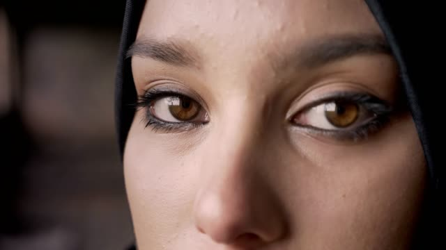 close portrait of young muslim woman's eyes looking at camera in hijab, sad and depressed expression - etnia medio orientale video stock e b–roll