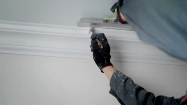 close shot at a builder hands, a man doing repairs in an apartment, people paint a brush with a molding on the ceiling a professional builder wearing gloves, who works at the apartment, is engaged in painting the molding, the person is holding a brush and a spatula in his hand to work with the ceiling on which there is a gypsum molding a shape stock videos & royalty-free footage