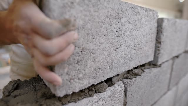 close shot at the bricklayer's hands, the builder puts the bricks, using a stretched string for an even level of masonry materials - mattone video stock e b–roll