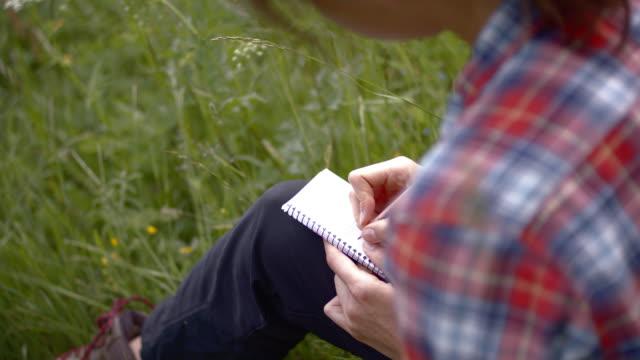nahaufnahme einer jungen frau, die in hohem gras auf einem notizblock sitzt - eskapismus stock-videos und b-roll-filmmaterial