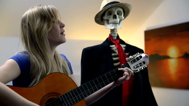 Close shot of female playing something to bones Woman plays the acoustic guitar and sings songs to entertain the sitting skeleton animal skeleton stock videos & royalty-free footage