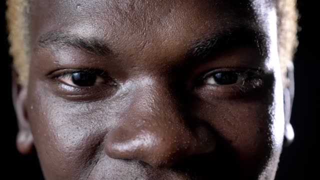 close shot of happy african american man's eyes looking at camera, black background in studio - vicino video stock e b–roll