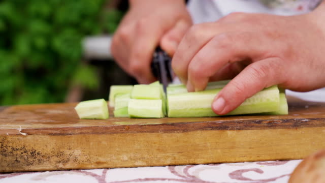 close shot of man hands cutting cucumber with a knife on wooden board - cetriolo video stock e b–roll