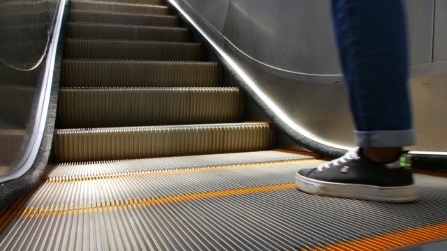 close shot of outdoor escalator with parts of a person going upwards - escalator video stock e b–roll