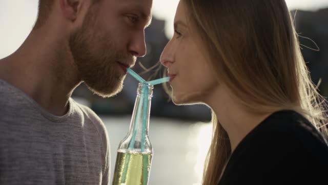 vídeos de stock e filmes b-roll de close shot of sweet couple drinking lemonade with a straw - limonada tradicional