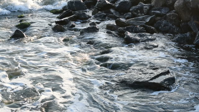 Close shot of waves rolling over rocks on a beach. video