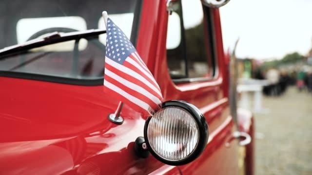 vídeos de stock, filmes e b-roll de feche a vista lateral da picape vermelha com pequena bandeira americana acenando em câmera lenta de slo-mo - caminhonete pickup