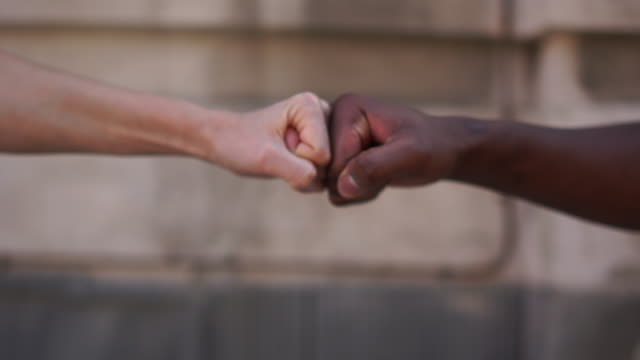 close up a black fist and a white fist clashed in a clinch against a wall. no racism, tolerance and political correctness in society. us protests - rispetto video stock e b–roll