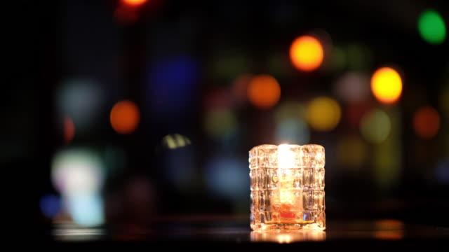chiudere una candela in vetro sul tavolo. sfoca le luci colorate su sfondo scuro. - soft focus video stock e b–roll