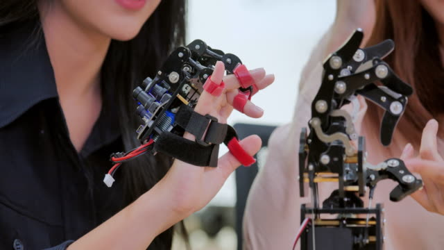 Close up a futuristic Prosthetic Robot Arm by a teenage girl having fun of development engineer in a research laboratory.Arm moves its fingers.Industry 4.0.Education,technology,teamwork,science and people concept. Education Topics :Close up a futuristic Prosthetic Robot Arm by a teenage girl having fun of development engineer in a research laboratory.Arm moves its fingers.Industry 4.0.Education,technology,teamwork,science and people concept. prosthetic equipment stock videos & royalty-free footage