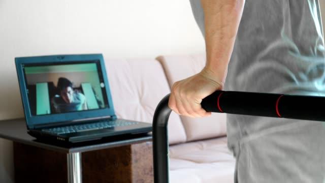 närbild. en ung man bedriver online-utbildning hemma. visar motion dips skytte för webbkamera av den bärbara datorn. fjärrarbete under karantänen. - balettstång bildbanksvideor och videomaterial från bakom kulisserna