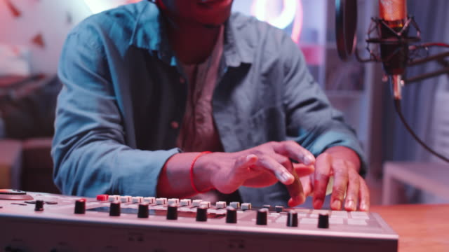vídeos de stock e filmes b-roll de close up afro-american man using mixing console and recording music - músico