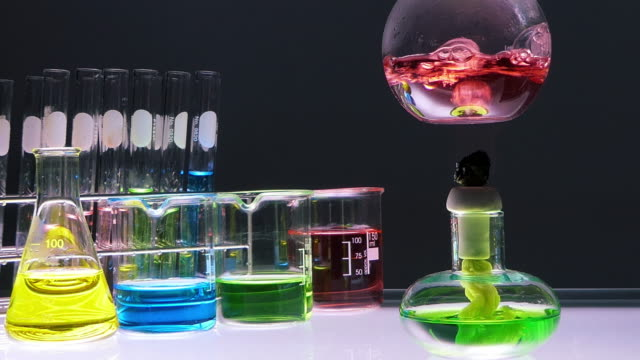 yakın alkol lambası siyah arka plan üzerinde laboratuvar cam ile şişe kırmızı kimyasal sıvı kaynatıyor. laboratuvar araştırma ve geliştirme konsepti. - kimya stok videoları ve detay görüntü çekimi
