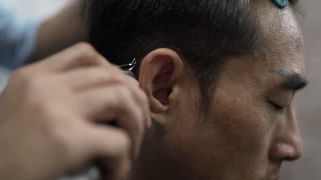 Close up, Asian Chinese male hairdresser using classic razor shave man's hair in Saloon. Barber shop.