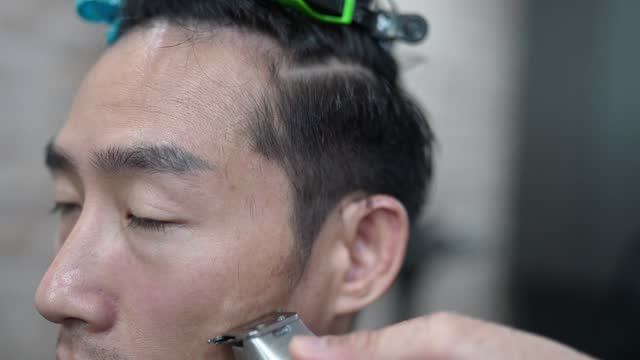 Close up, Asian Chinese male hairdresser using hair clipper shave man's hair in Saloon. Barber shop.