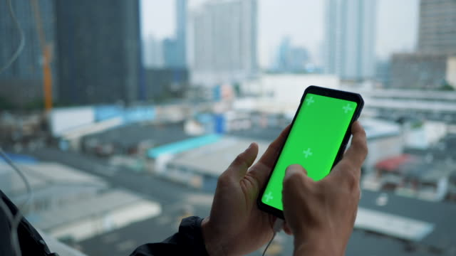 Close up Asian Man holds a blank Green Screen smart device, Using Android Phone. Bangkok city.