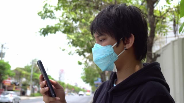 Close up asian man with green hygienic mask prophylactic using smartphone. Health and care concept.