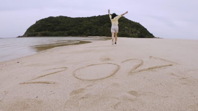 närmjut asiatisk kvinna hoppa över 2021 nytt år och kör på sand med armen upp på stranden och ön - calendar workout bildbanksvideor och videomaterial från bakom kulisserna