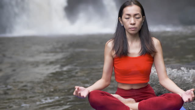 Close up Asian woman practicing or doing yoga at the waterfall, Lotus pose on meditation session. Beautiful Landscape, Natural background, Thailand. doing, experienced, fit fitness, pose, posture practice, professional, wellness, workout yoga, practicing yoga, Front View lotus position stock videos & royalty-free footage