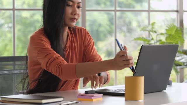 vídeos de stock e filmes b-roll de close up asian woman rearrange stuff on desk and closed laptop when finish working at home - arranjo