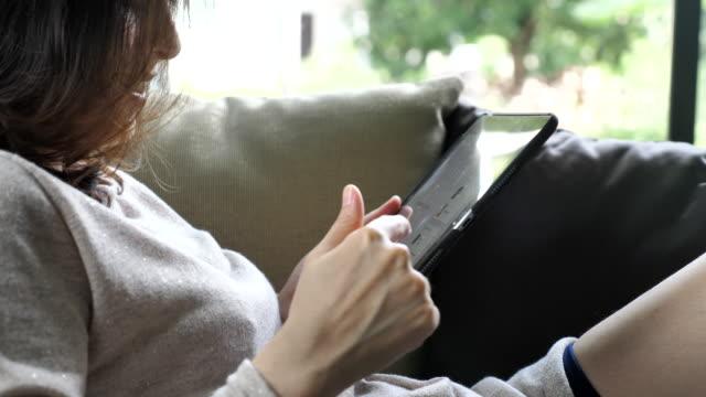 Gros plan femme asiatique touchant un tablet PC - Vidéo